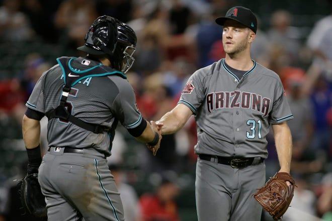 Aug 14, 2018: Arizona Diamondbacks catcher Alex Avila (5) congratulates relief pitcher Brad Boxberger (31) after defeating the Texas Rangers at Globe Life Park in Arlington.
