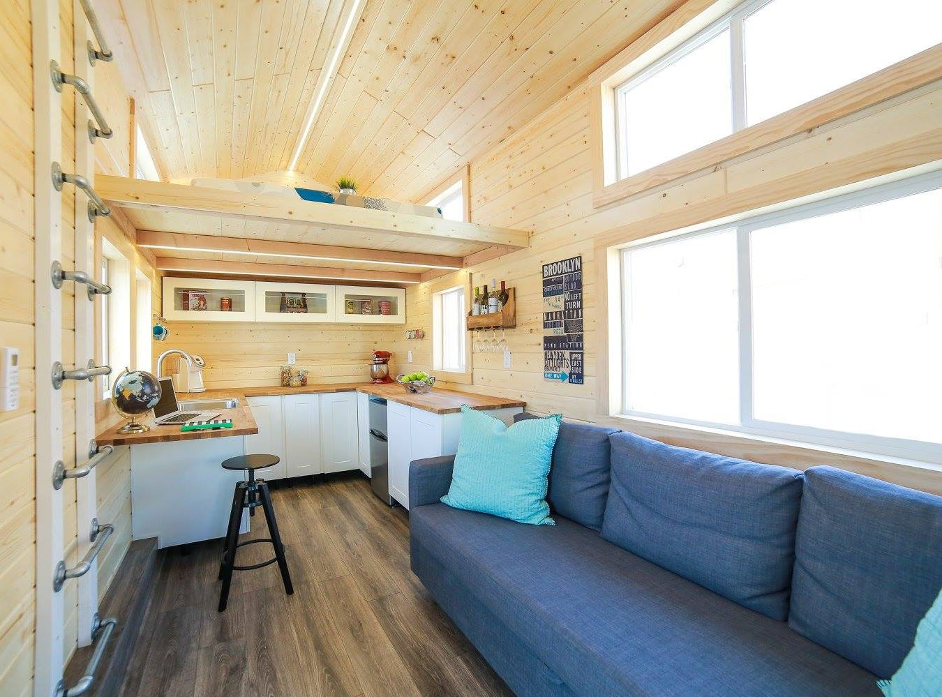 A view of the living room leading into the kitchen inside a tiny home.