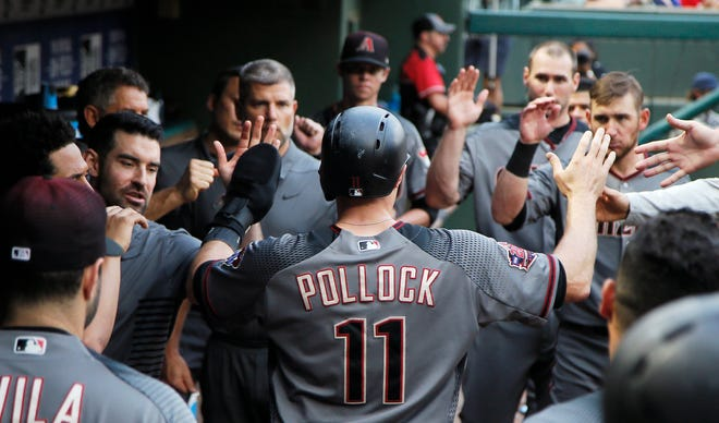 Arizona Diamondbacks' A.J. Pollock (11) is congratulated by teammates after scoring on an RBI double hit by Steven Souza Jr., not pictured, during the first inning of a baseball game against the Texas Rangers, Monday, Aug. 13, 2018, in Arlington, Texas. Texas won 5-3.
