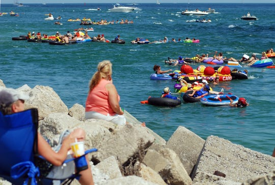 Spectators watch from the shoreline near the Blue Water Bridge as thousands of tubers float by in the 2008 Port Huron Float Down.