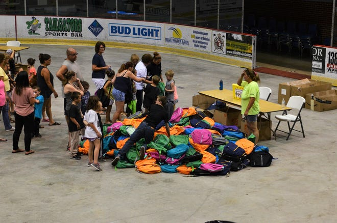 Volunteers hand out backpacks in a variety of colors during Port Huron's 16th annual backpack giveaway on Aug. 15, 2018, in Port Huron.