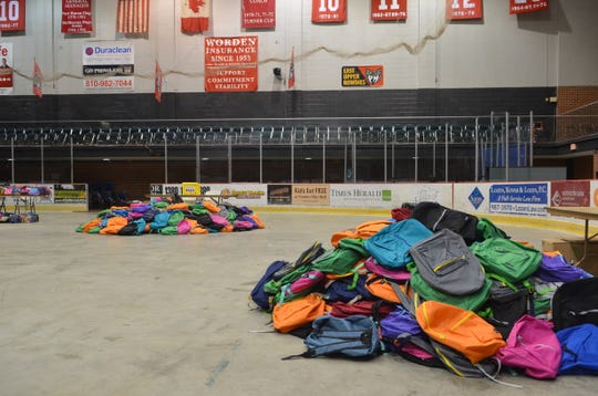 Backpacks are sorted into piles for middle and elementary school students at Port Huron's 16th annual backpack giveaway on Aug. 15, 2018, in Port Huron.