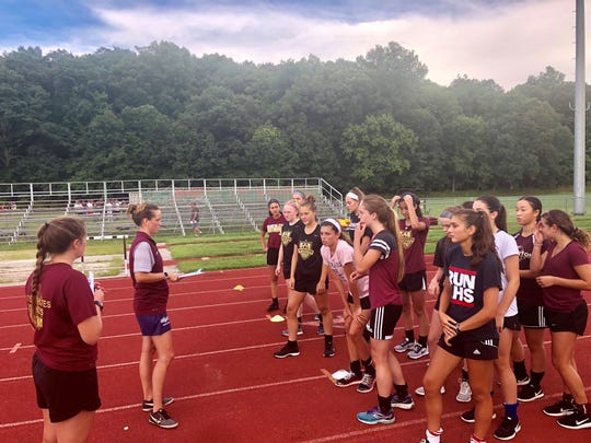 Arlington coaches Kelley Hand and Biz LaTuso address the girls soccer team during practice on Tuesday.