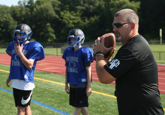 Head coach, Sean Keenan leads a drill during Wednesday's pre-season practice at Millbrook High School on August 15, 2018.