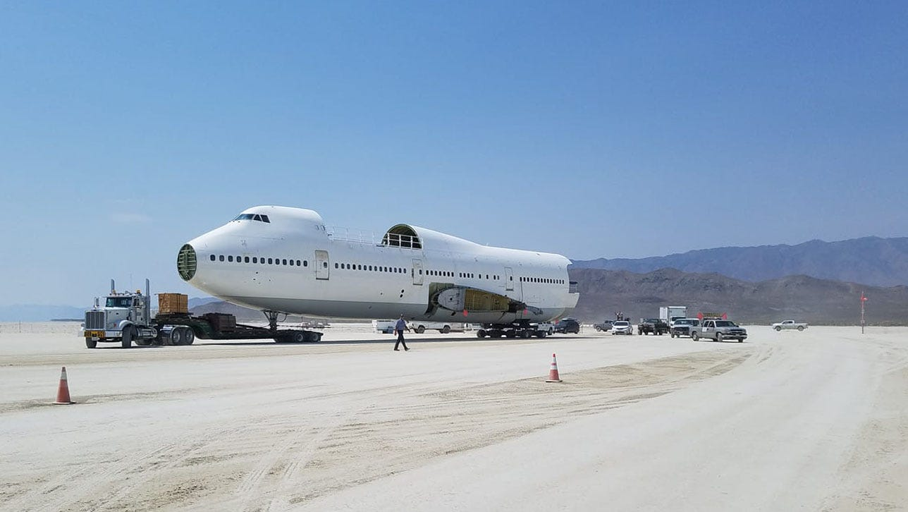 Burning Man camp Big Imagination hauled a partially reconstructed 747 aircraft onto the playa morning of Aug. 14, 2018. The wings will be shipped in separately. The airplane was registered as an art car and plans to be towed around the playa this year and will house a club and bar. The project is four years in the making.