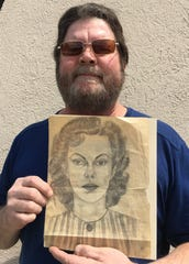 William Hakala of Reno holds a pencil-on-paper portrait of a woman, dated 1940, that he found under a Reno thrift-store painting.