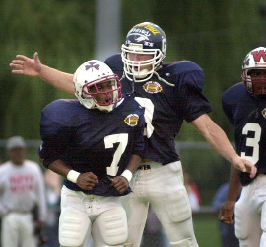 West All-Star defensive teammates Kassim Howell from Aquinas Institute (7), left, and Mike Latek from Eastridge celebrate a play in the first half of the 18th Annual Eddie Meath All-Star Game at Webster High School on Aug. 6, 2000.