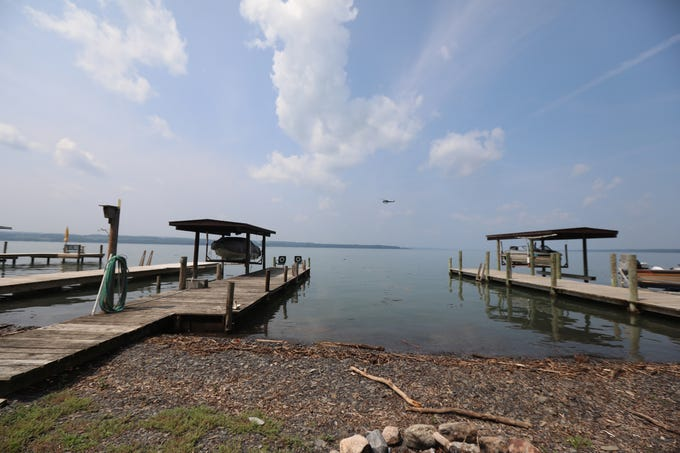 A NY State Police helicopter flies low along the shoreline at Lodi Point, New York surveying the damage on Thursday, August 15, 2018.  A line of debris could be seen several feet out from Seneca Lake shoreline.