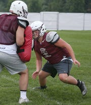 Aquinas center Nick Annechino, right, explodes off his line and into the block of teammate Tyson Foster, left, during practice on Aug. 15, 2018.