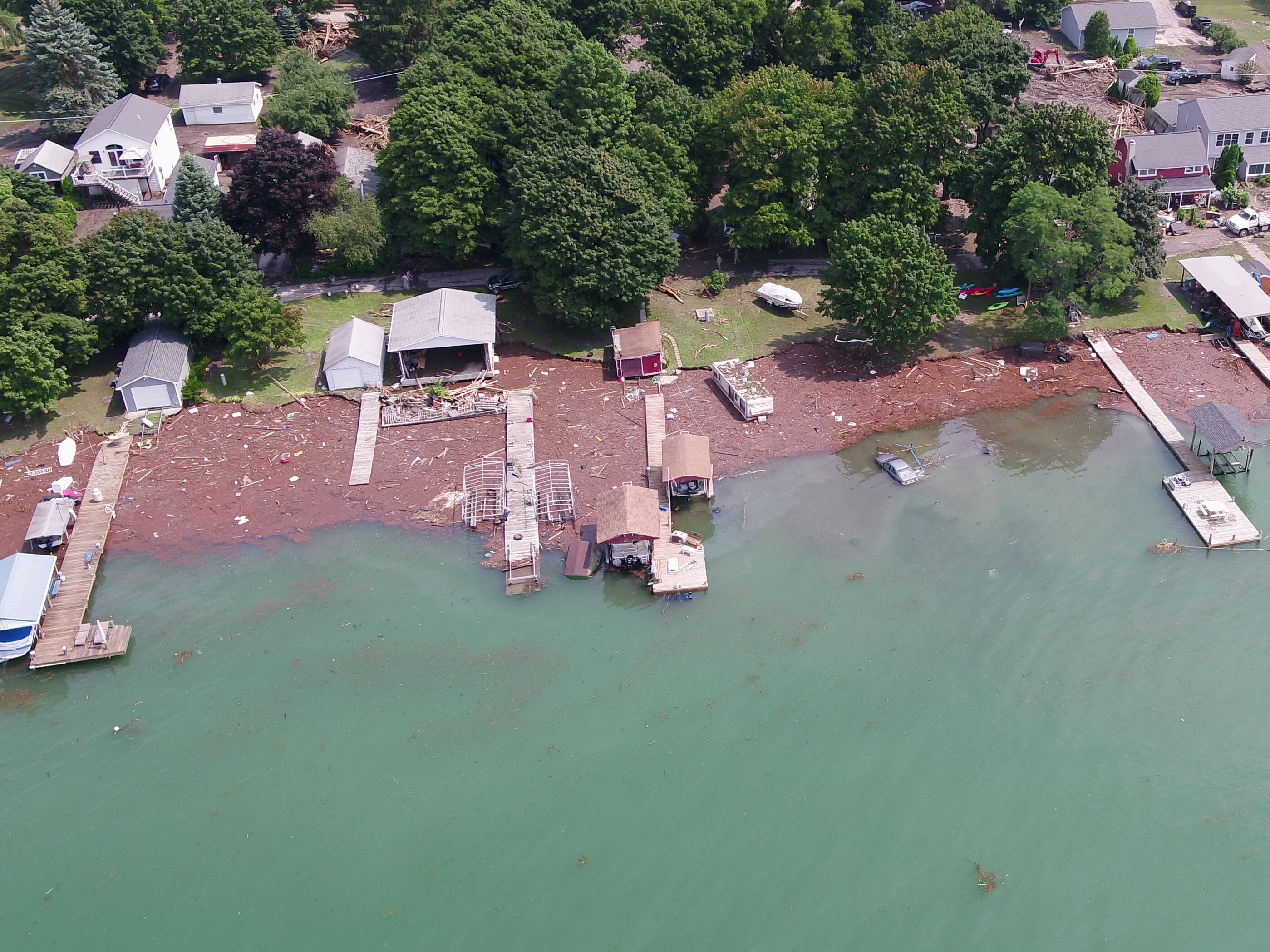 An aerial view of the Seneca Lake shore north of Lodi Point Marine Park shows the damage, including a car submerged in the lake, from Tuesday's flooding. This image was captured from the Democrat and Chronicle's unmanned aircraft system on Wednesday.