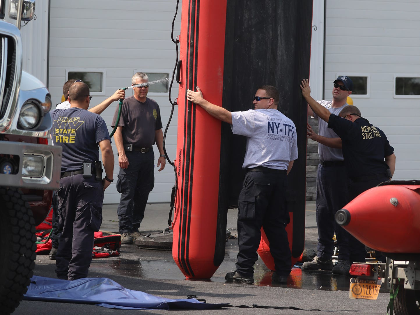 Emergency workers gather at the Ovid Fire Department and help clean equipment that was used to rescue stranded residents.
