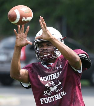 Aquinas wide receiver Damon Montgomery looks in a reception.