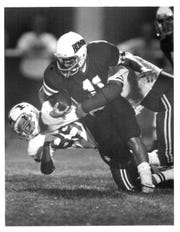 East Rochester quarterback Geoff Mandile is tackled by two Hilton players, including Scott Thomas (89) after breaking a run into the secondary during a game played on Sept. 11, 1987. Mandile is now the varsity football coach at Victor.