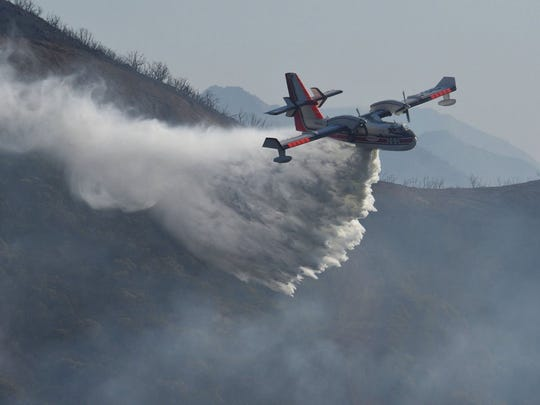 In this file photo provided by the Santa Barbara County Fire Department, a Bombardier 415 Super Scooper makes a water drop on hot spots along the hillside east of Gibraltar Road in Santa Barbara, Calif., Sunday morning, Dec. 17, 2017. Two Super Scooper planes stationed in Chico are available to fight the Hirz Fire near Lake Shasta once the smoke clears, according to the U.S. Forest Service