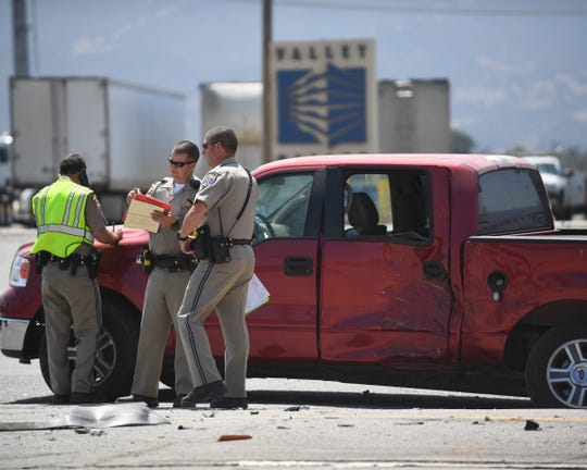 California Highway Patrol officers work at a scene involving a cargo truck that hit a pickup truck turning onto Highway 101 Wednesday. A child was flown out from the scene with major injuries.