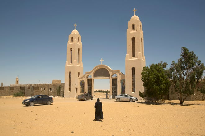 In this May 27, 2017 file photo, a priest walks in front of St. Samuel the Confessor Monastery in Maghagha, Egypt. The killing of a respected bishop in a desert monastery north of Cairo has opened a rare window onto the cloistered world of Egypt's Coptic Orthodox Church. It's one of the oldest Christian communities in the world and the one that introduced monasticism to the faith. But the killing of the abbot, and the arrest of two monks suspected in his death, has shaken the church.