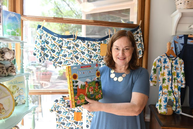 Barefoot Baby Boutique owner Martha Ogburn holds some of the music themed items that she will be offering in her downtown Salisbury store during the National Folk Festival.
