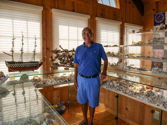 Larry Mann stands near his 7-continent seashell collection in his Rehoboth Beach home.