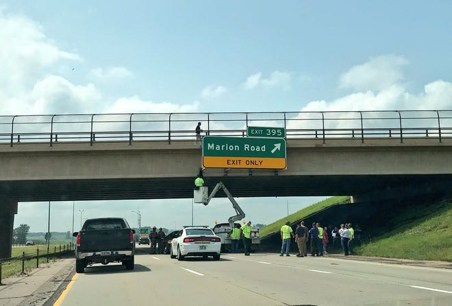Crews and law enforcement work on I-90 at the Marion Road exit, where someone reportedly jumped from the overpass.