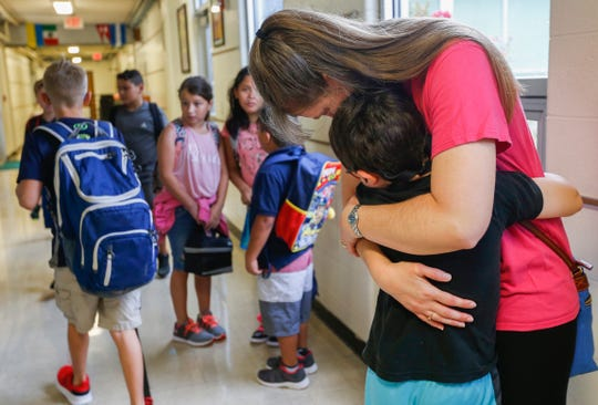 Regina Tracy hugs her son Jonah Tracy, 8,  on the first day of school at Wilder Elementary School on Wednesday, Aug. 15, 2018.