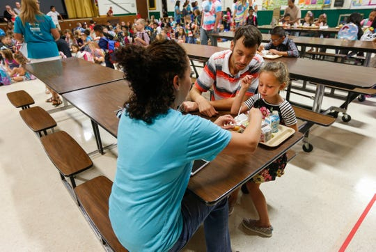 Greer Hudson, a kindergartener at Wilder Elementary School, eats breakfast with her parents, Mark and Juliana Hudson, on the first day of school on Wednesday, Aug. 15, 2018.