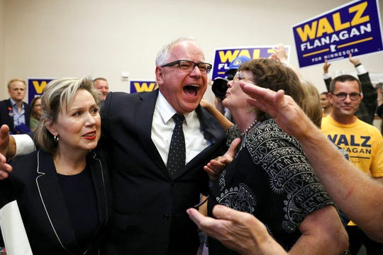 Minnesota DFL gubernatorial candidate Tim Walz, center, along with his wife, Gwen, left, celebrates with supporters after it was announced he had won the primary during a watch party at the Carpenters Union Hall in St. Paul, Minn., Tuesday, Aug. 14, 2018. (Anthony Souffle/Star Tribune via AP)