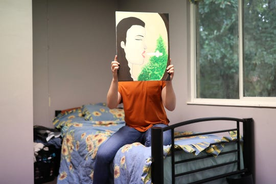 """Julia,"" a pseudonym for the 17-year-old girl who wished to remain anonymous, holds one of her paintings as she sits on her bed at Capital City Youth Services. ""The word transgender was not in my vocabulary because of where I was,"" said Julia, who comes from a rural Florida community. Though in third grade she says she approached a school resource officer and said out loud for the first time: ""I feel like I might be a female trapped in a male's body."""