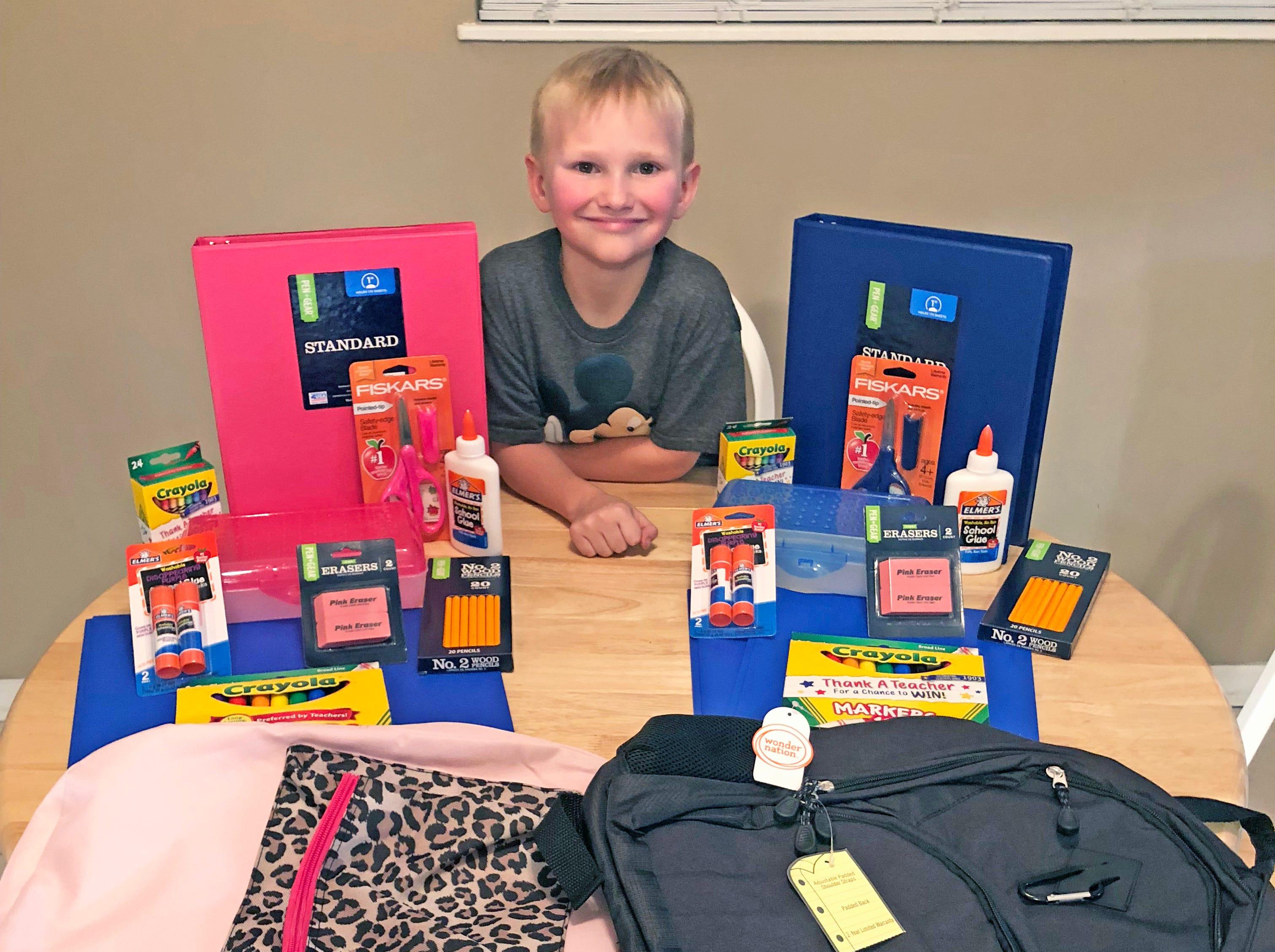 Corbin Odekirk preparing to fill backpacks for school children in need.
