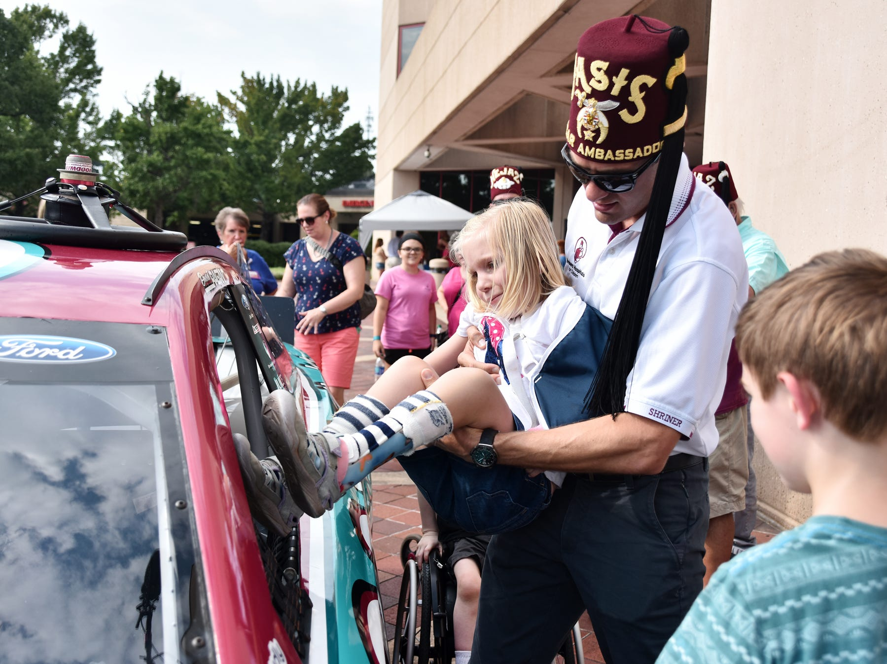 NASCAR driver David Ragan helps Ana Pabst, 5, into a race car at the Shriners Hospital for Children in Greenville on August 15, 2018.