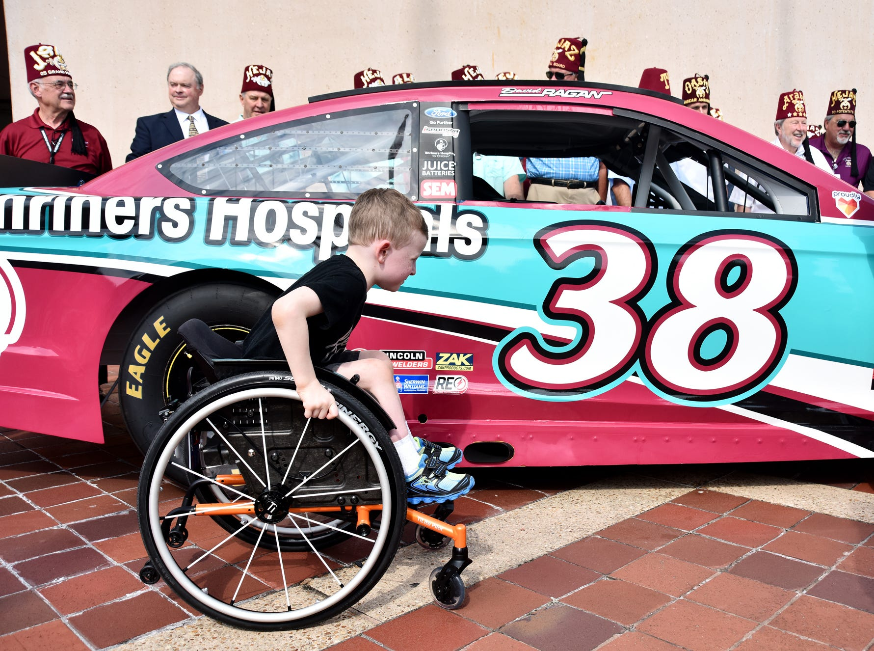 Wyatt Banks, 5, pushes his wheelchair past a  race car at the Shriners Hosptial for Children in Greenville on August 15, 2018.