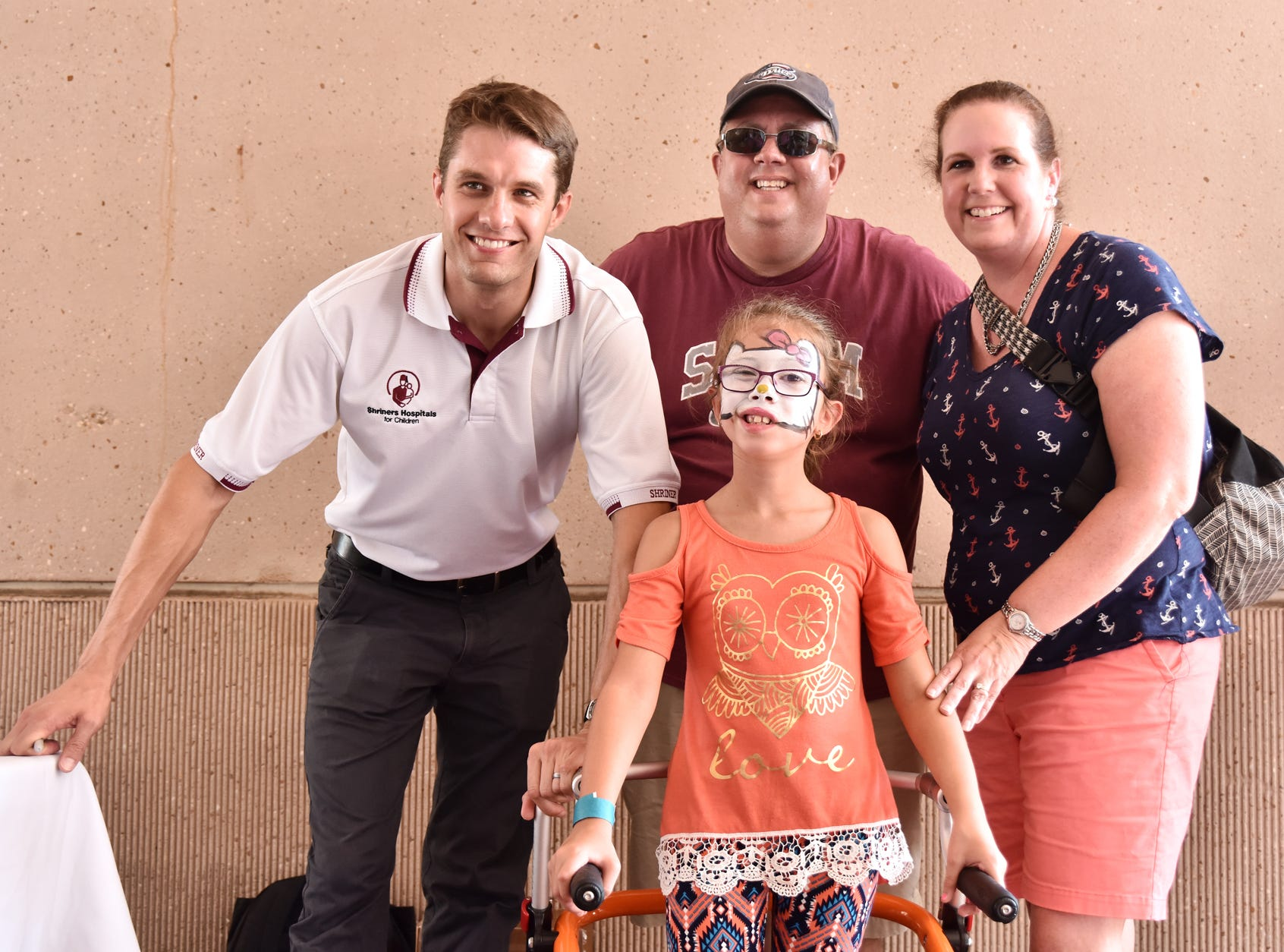 A family poses for a photo with NASCAR Driver David Ragan at the Shriners Hospital for Children in Greenville on August 15, 2018.