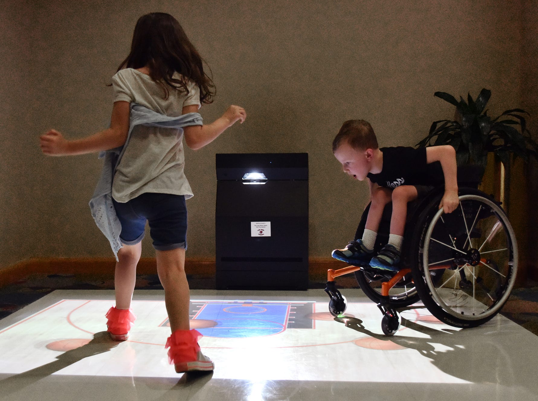 Wyatt Banks, 5, right, and his sister Austin, 7, play on an interactive floor at the Shriners Hospital for Children in Greenville on August 15, 2018.