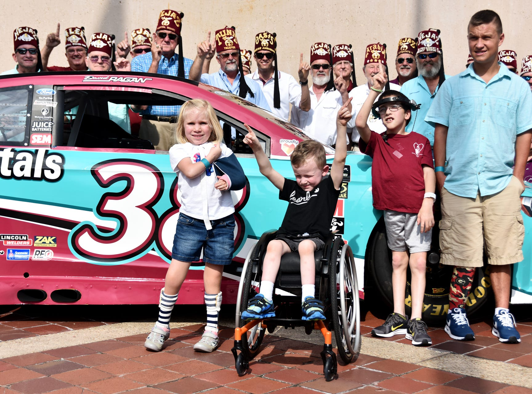 Children and shriners pose for a photo with NASCAR Driver David Ragan at the Shriners Hospital for Children in Greenville on August 15, 2018.