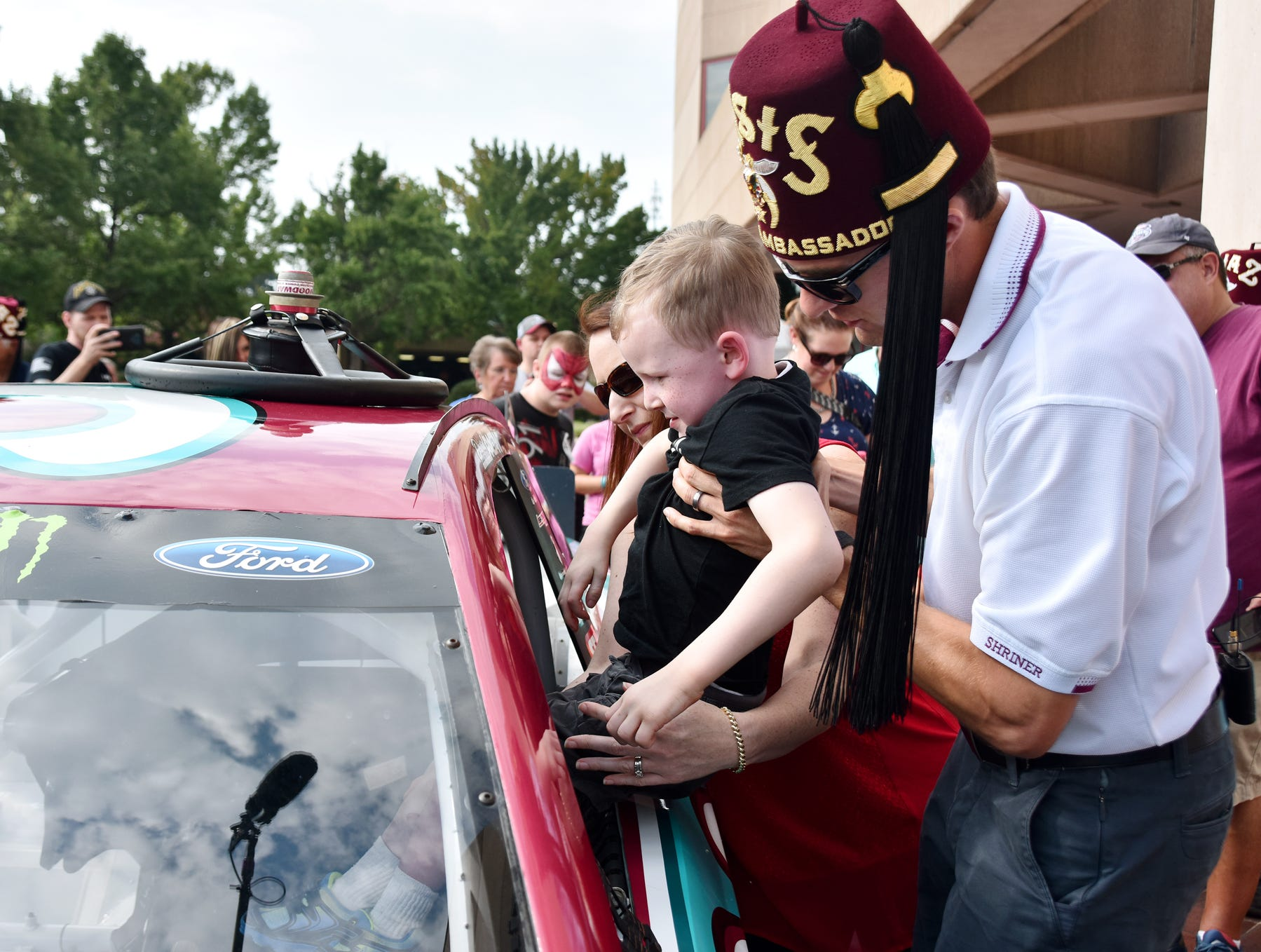 NASCAR driver David Ragan helps Wyatt Banks, 5, into a race car at the Shriners Hospital for Children in Greenville on August 15, 2018.