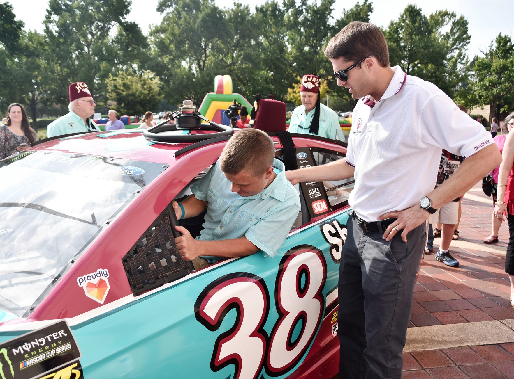 NASCAR driver David Ragan helps Landen Vaughan, 15, into a replica car at the Shriners Hospital for Children in Greenville on August 15, 2018.