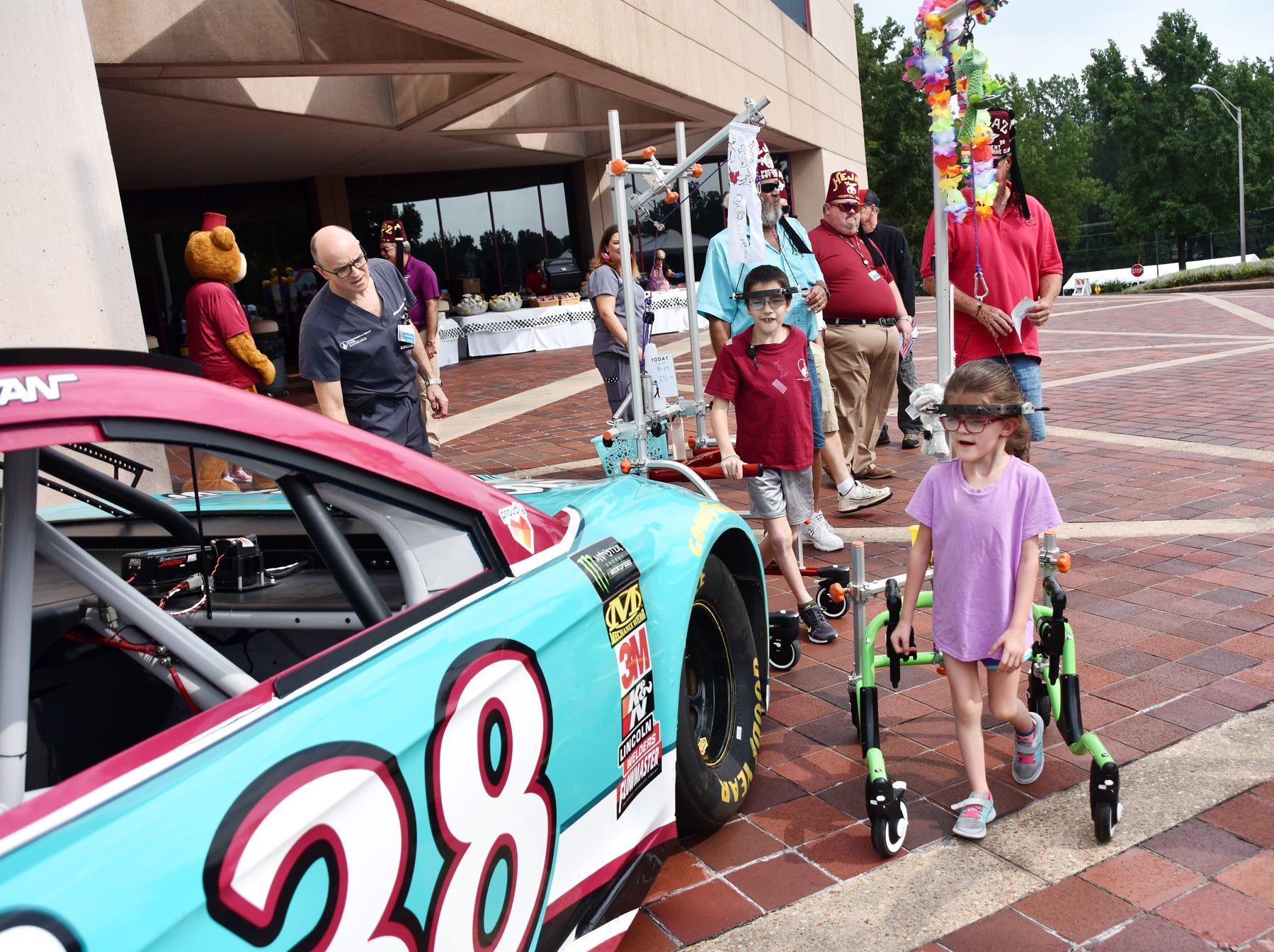 Children walk towards a race car at the Shriners Hospital for Children in Greenville on August 15, 2018.