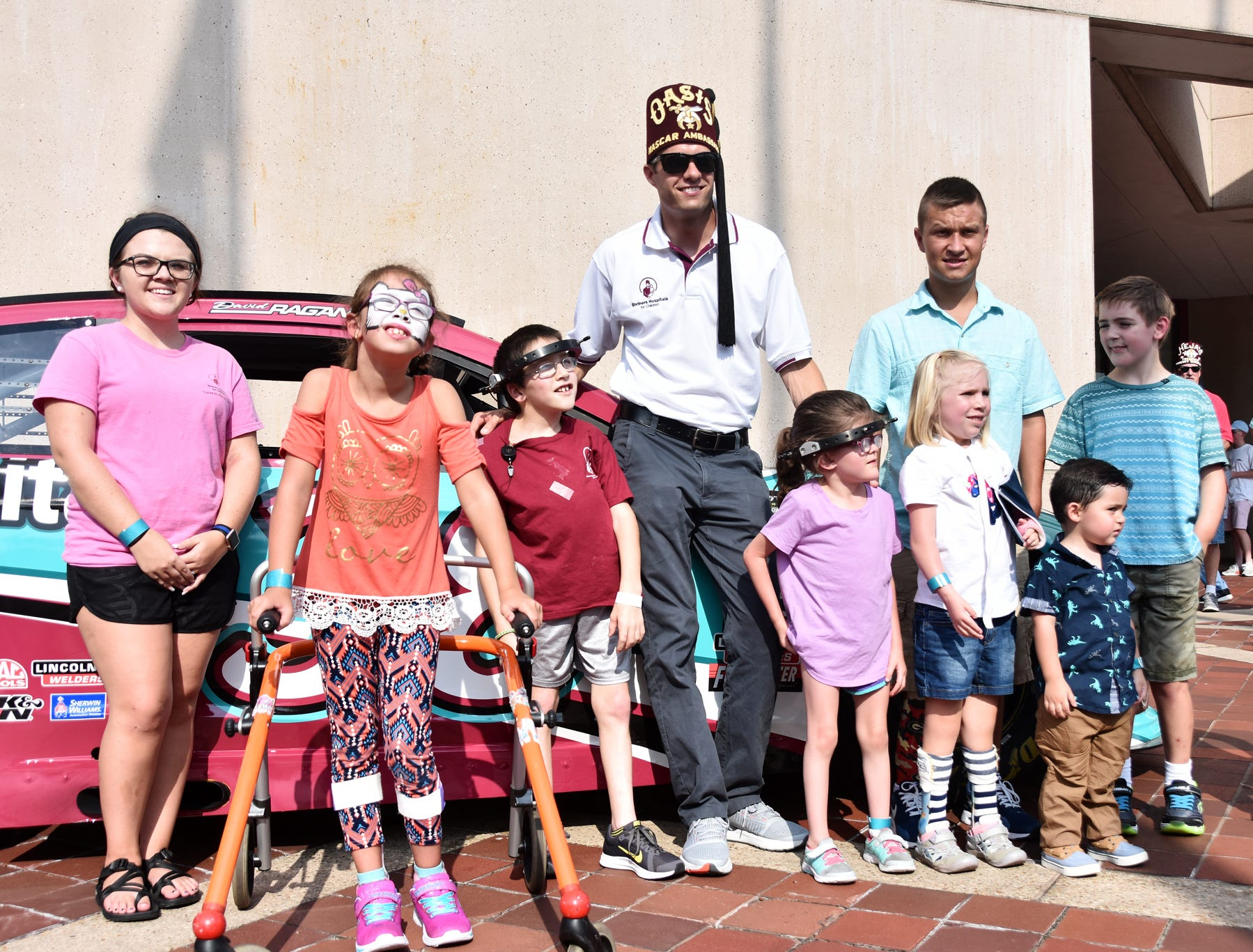 Children pose for a photo with NASCAR Driver David Ragan at the Shriners Hospital for Children in Greenville on August 15, 2018.