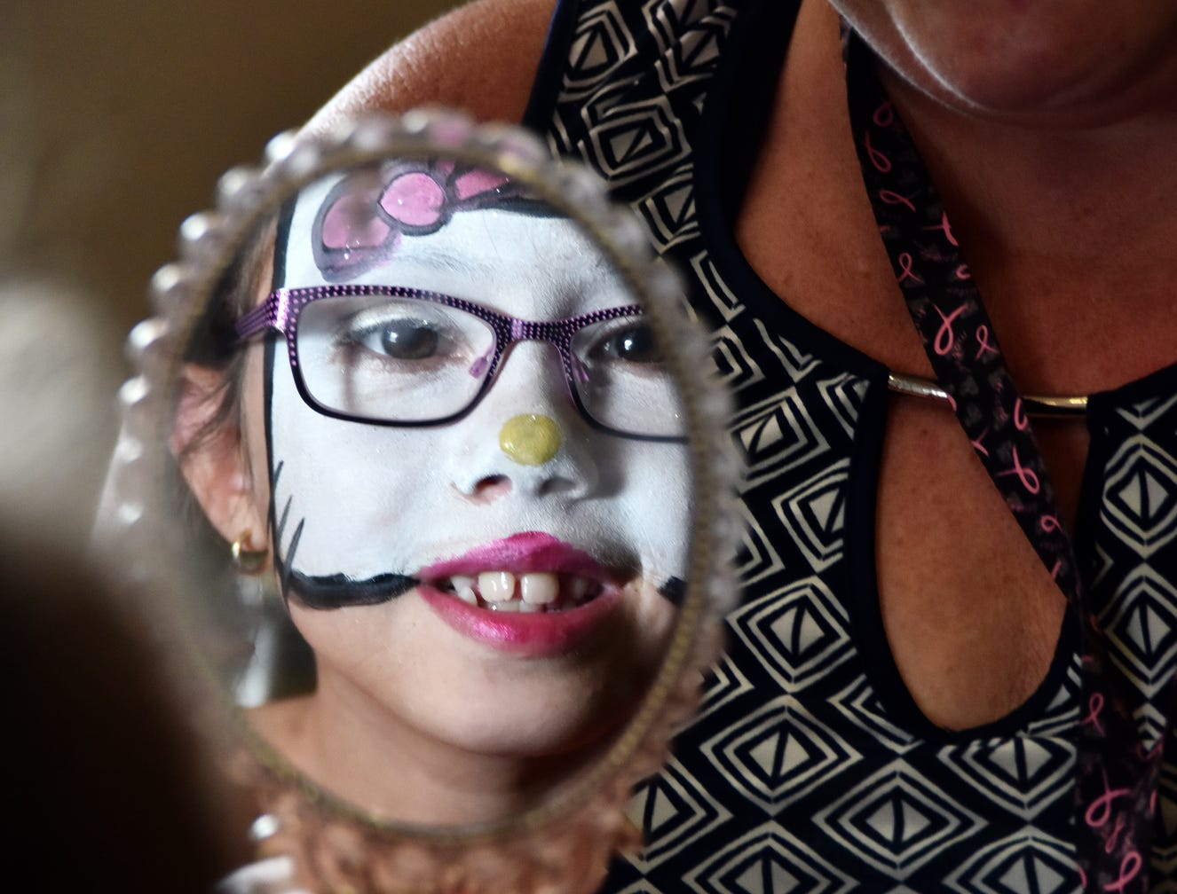 Ellie Barbour, 8, looks into a hand mirror after having her face painted at the Shriners Hospital for Children in Greenville on August 15, 2018.