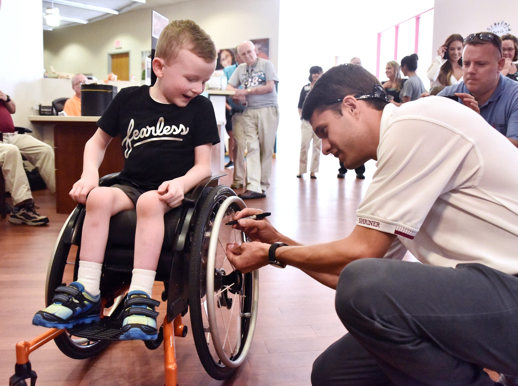 Wyatt Banks, 5, has his wheelchair signed by NASCAR driver and Shriner David Raga at the Shriners Hosptial for Children in Greenville on August 15, 2018.