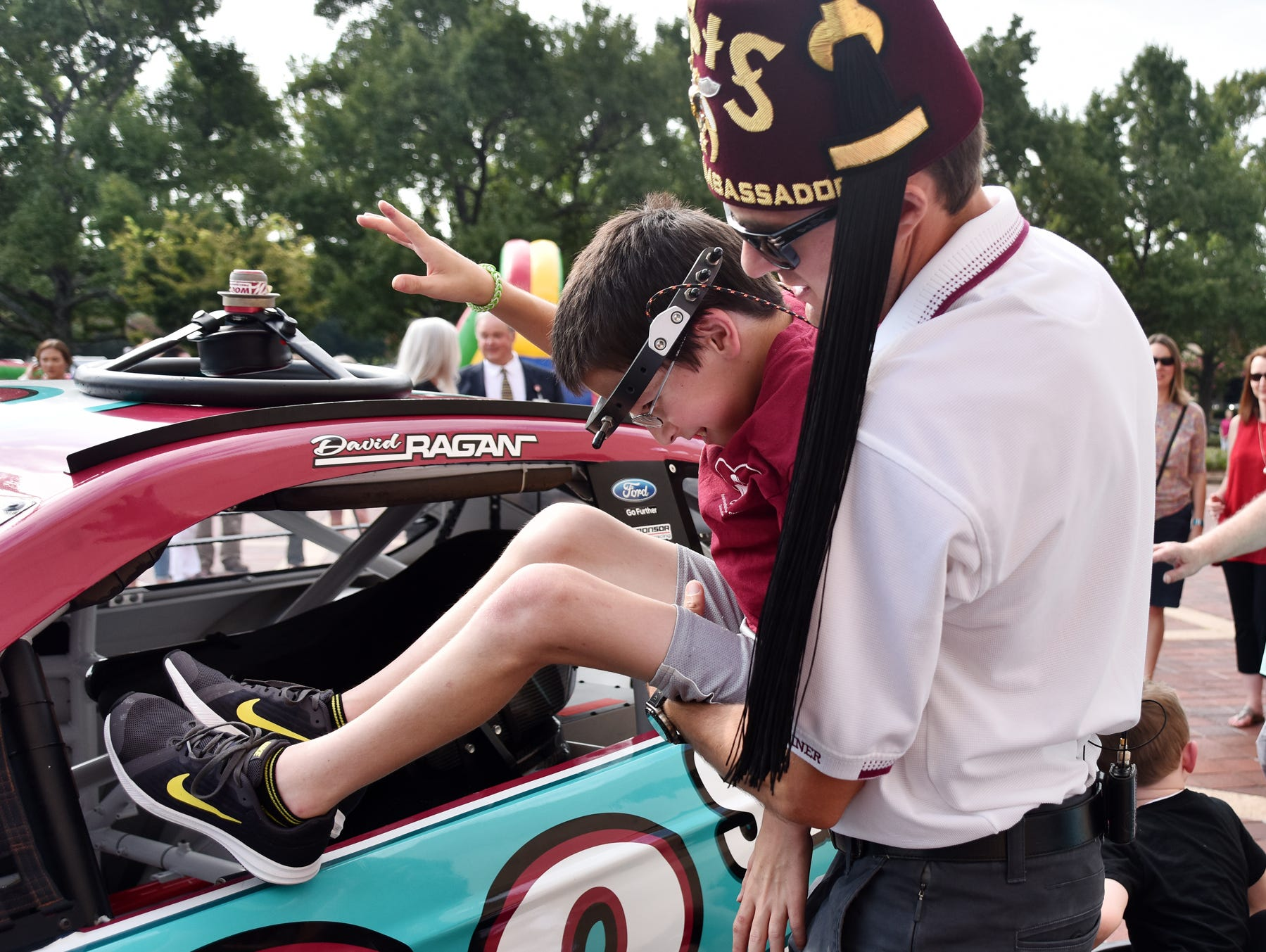 NASCAR driver David Ragan helps Grayson Lusk, 11, into a race car at the Shriners Hospital for Children in Greenville on August 15, 2018.