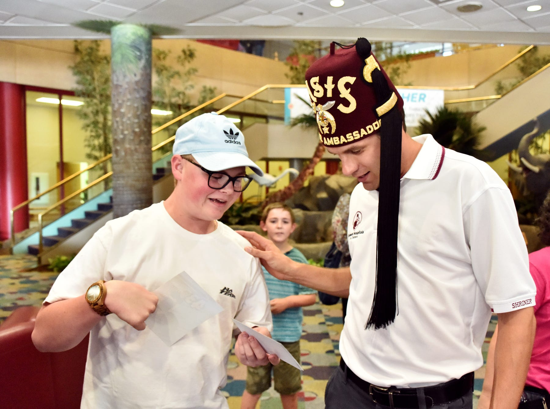 Chase Plesko, 15, left, talks with NASCAR driver David Ragan at the Shriners Hospital for Children in Greenville on August 15, 2018.