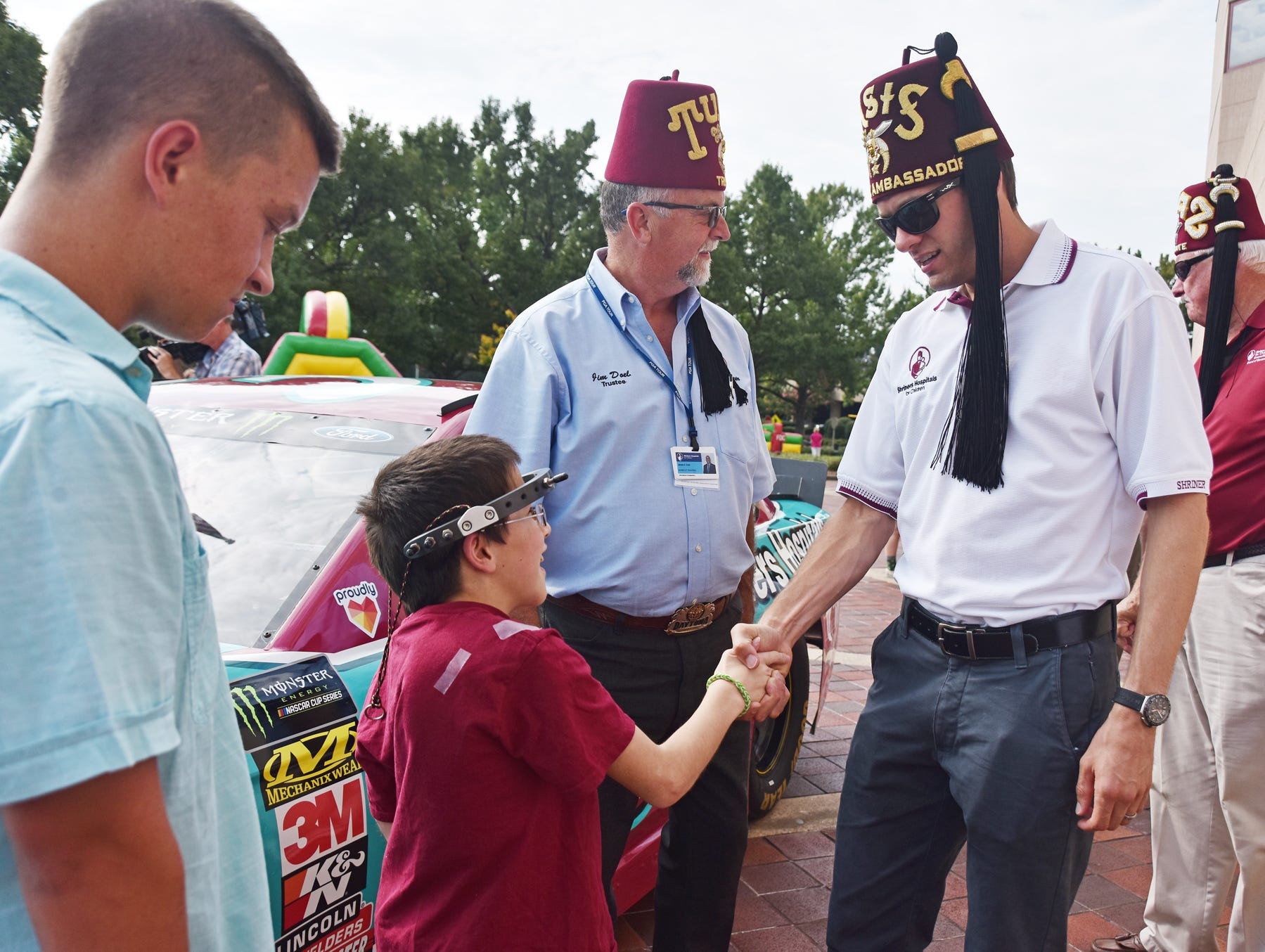 NASCAR driver David Ragan shakes hands with Grayson Lusk, 11, at the Shriners Hospital for Children in Greenville on August 15, 2018.