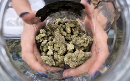 In this April 21, 2018, file photo, a bud tender displays a jar of cannabis at the High Times 420 SoCal Cannabis Cup in San Bernardino.