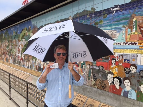 Jon Catalini of the Ventura County Star stands near a mural in Ventura giving away tickets to the Ventura County Fair.