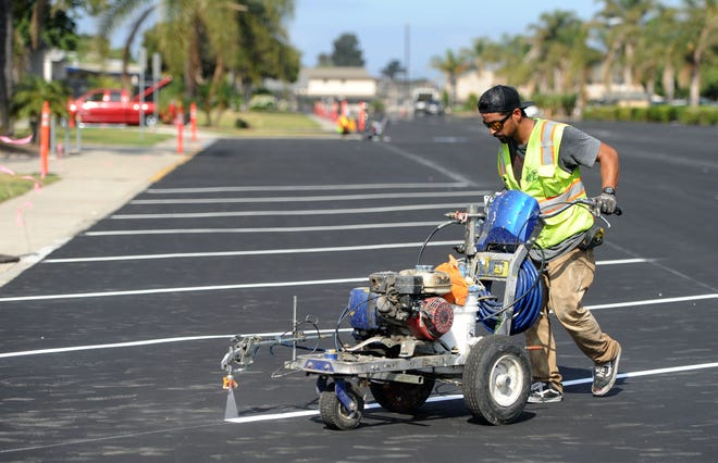 Issac Aceves from Pave West paints a white strip in the parking lot at Channel Islands High School. The Oxnard Union High School district worked on some maintenance projects over the summer in preparation for the new school year.