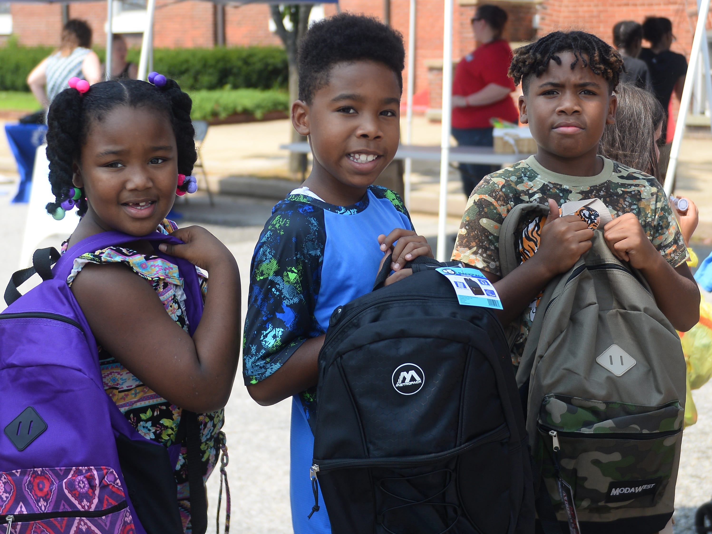 Children show off their new backpacks that they got for free at Millville's Play Streets event on Wednesday, August 15.