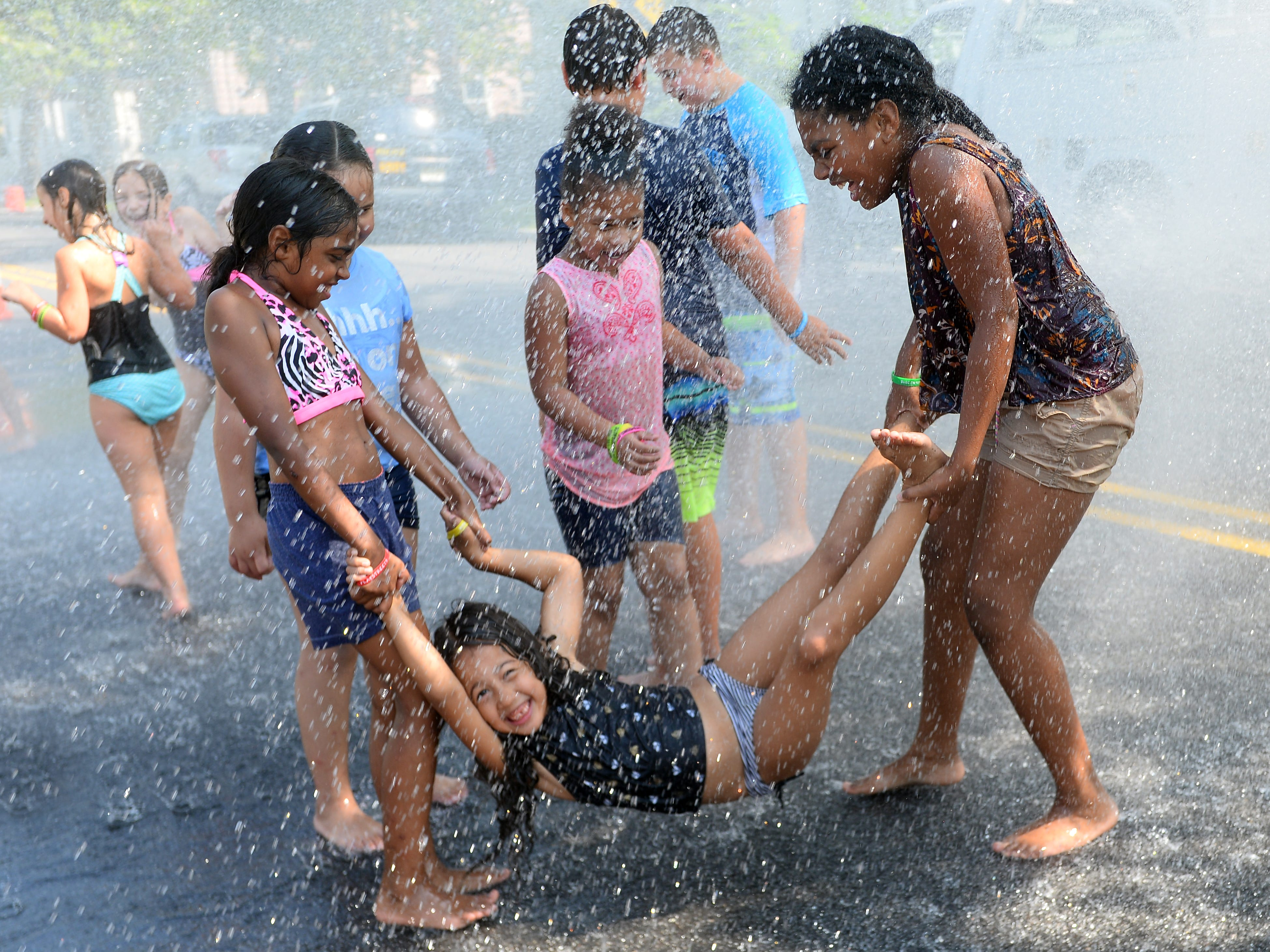 Children play in a hydrant opened by the city during Millville's free Play Streets event on Wednesday, August 15.