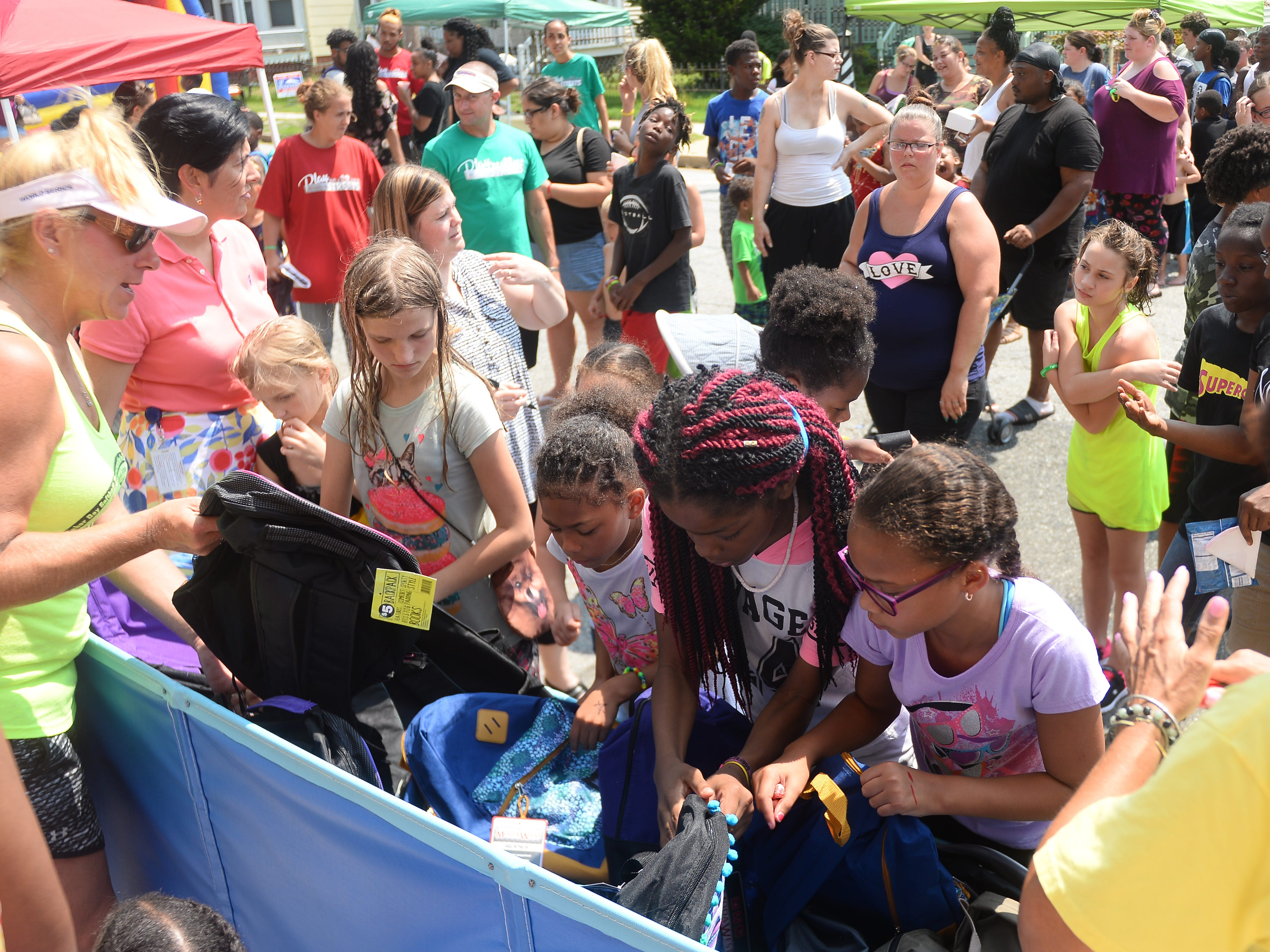 Children line up to pick out a free backpack at Millville's Play Streets event on Wednesday, August 15.