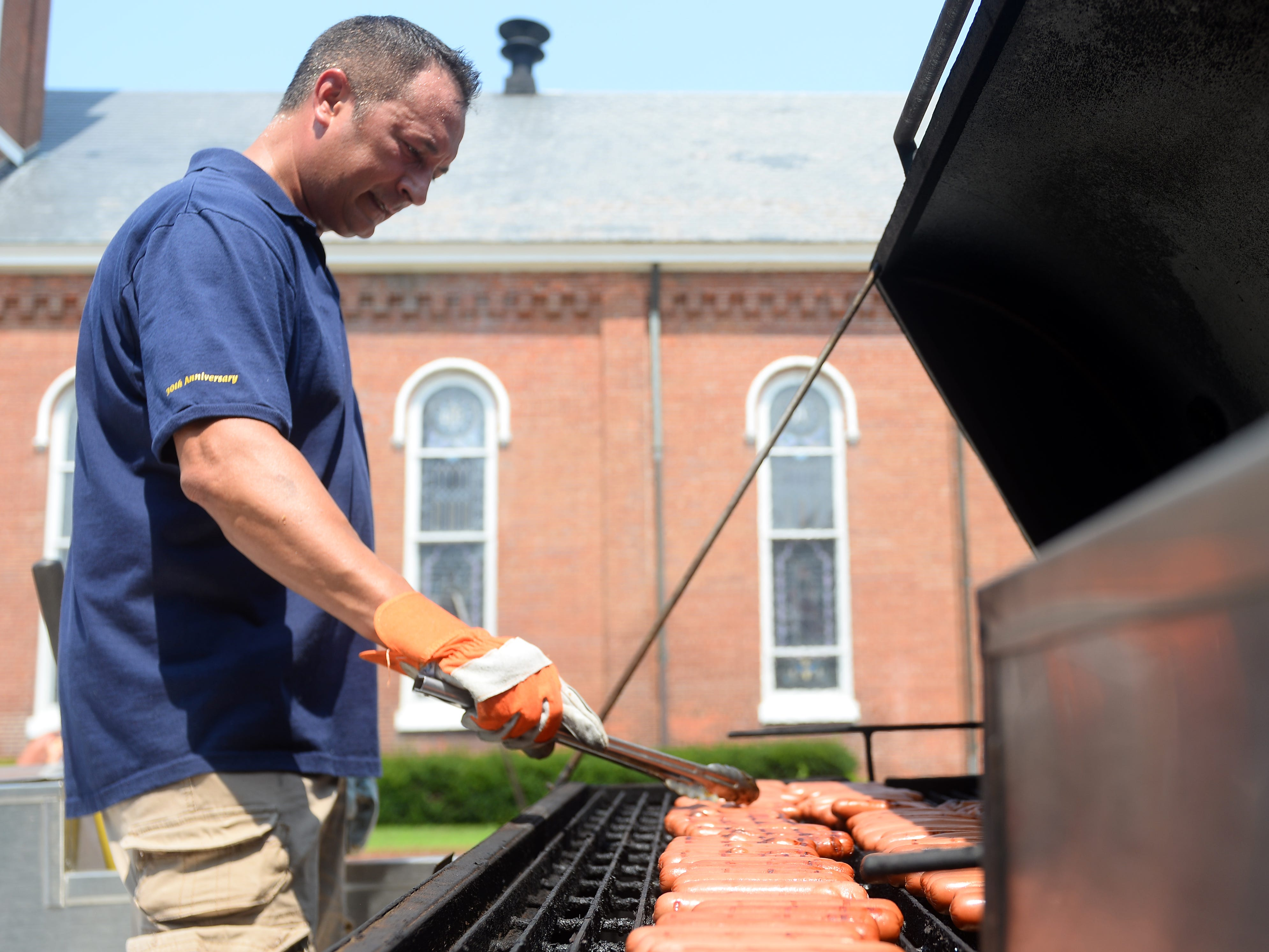 A Millville Play Streets volunteer cooks up some hotdogs during the event on Wednesday, August 15.