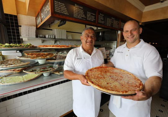 Rocco Rosano and his son Vinny Rosano hold the classic original cheese pizza at Rocco's at 170 South Main Street in New City, Aug. 15, 2018.